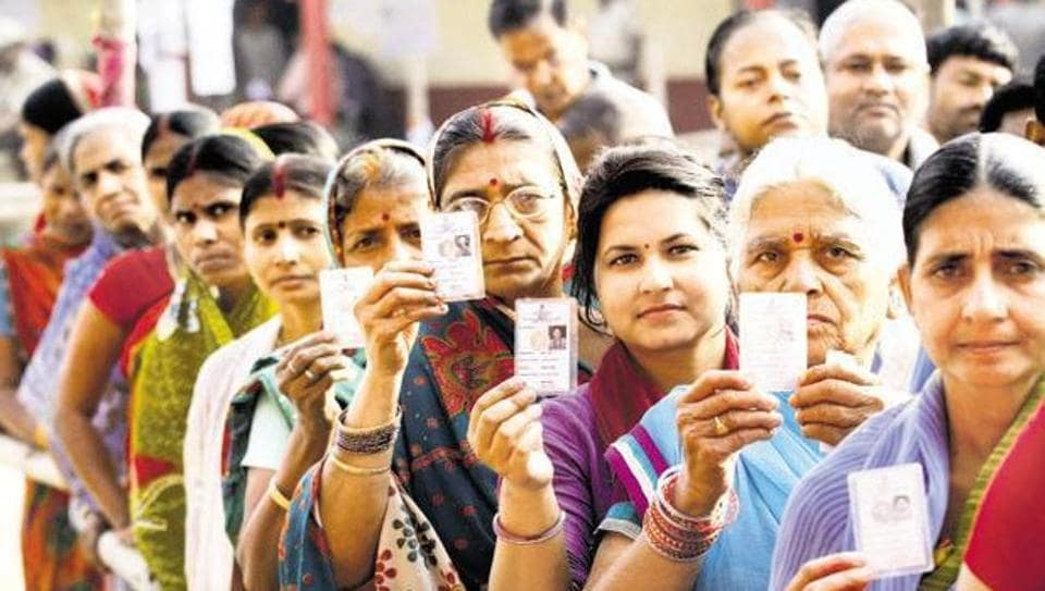 Voters queue up outside a polling booth.