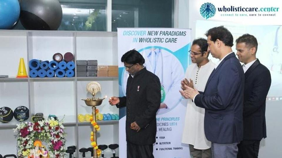 Dr. John Ebnezar lighting the auspicious lamp and inaugurating the Wholistic Care Center in Mumbai as Yogi Sakha, Dr. Pradeep Singh (centre) and Dr. Saurabh Talekar (extreme right) watches.