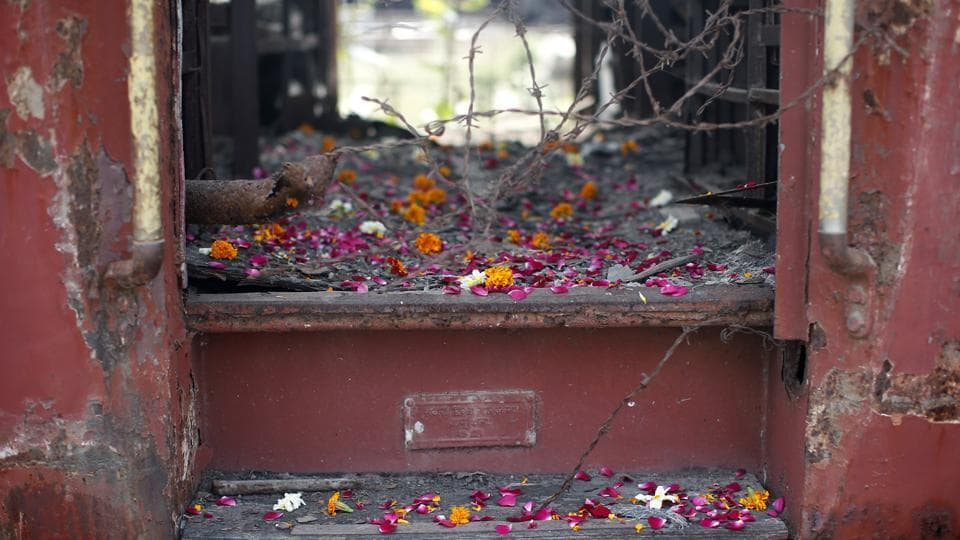 Flower petals scattered by the relatives of Godhra riots victims pictured at the doorsteps of a train carriage, that was set on fire in 2002, during the commemoration of the 12th anniversary of Godhra riots at Godhra.