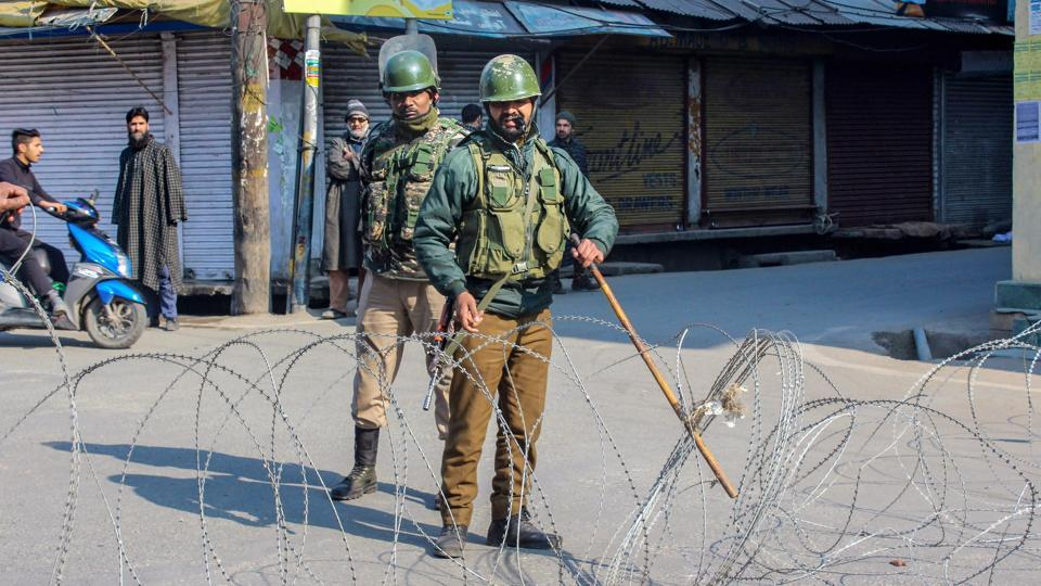 Security personnel stand guard at a blocked road  in Srinagar.