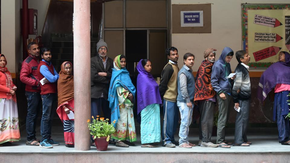 Voters stand in queues to cast their votes at a polling station, at St Giri Public School, Sarita Vihar, in New Delhi, India, on Saturday, February 8, 2020.