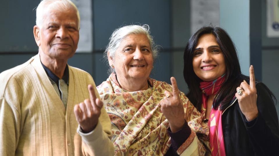 People show their finger marked with indelible ink after casting their vote during the Delhi Assembly election, at Civil Lines in New Delhi, India.