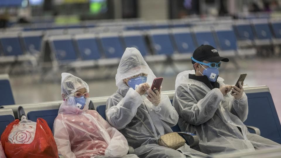 A family wearing masks and make-shift protection gear wait for their train at the Hongqiao High-speed Railway Station in Shanghai, China, on Tuesday, Feb. 11, 2020. The death toll from the coronavirus climbed above 1,000, as the Chinese province at the epicenter of the outbreak reported its highest number of fatalities yet.
