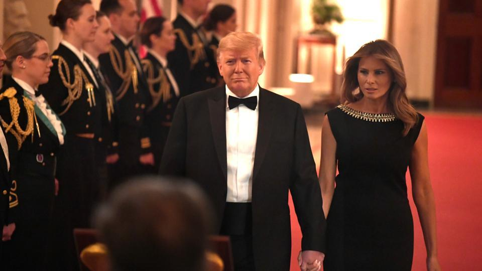 US President Donald Trump holds hands with first lady Melania Trump as they arrive to host the Governors Ball in the East Room of the White House, Washington.