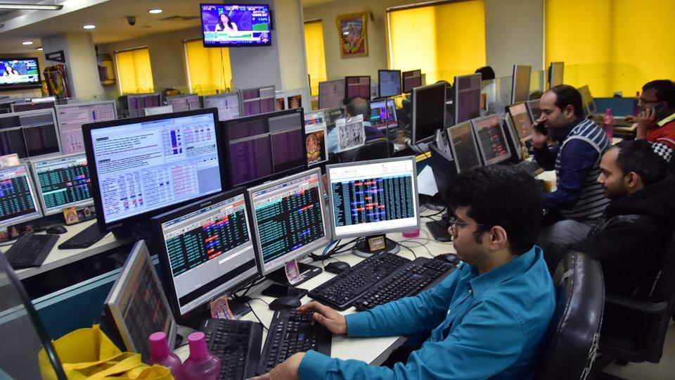 Traders work on the floor as Sensex and nifty reach highest in share market, in Kolkata on Thursday.