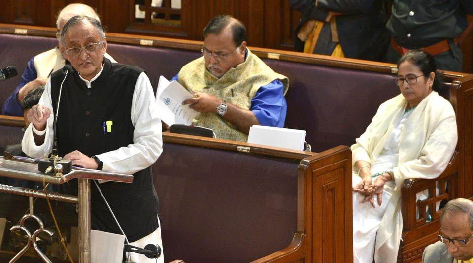 West Bengal State Finance minister Amit Mitra presents the state budget 2020-21 while Chief Minister Mamata Banerjee is seated behind him.