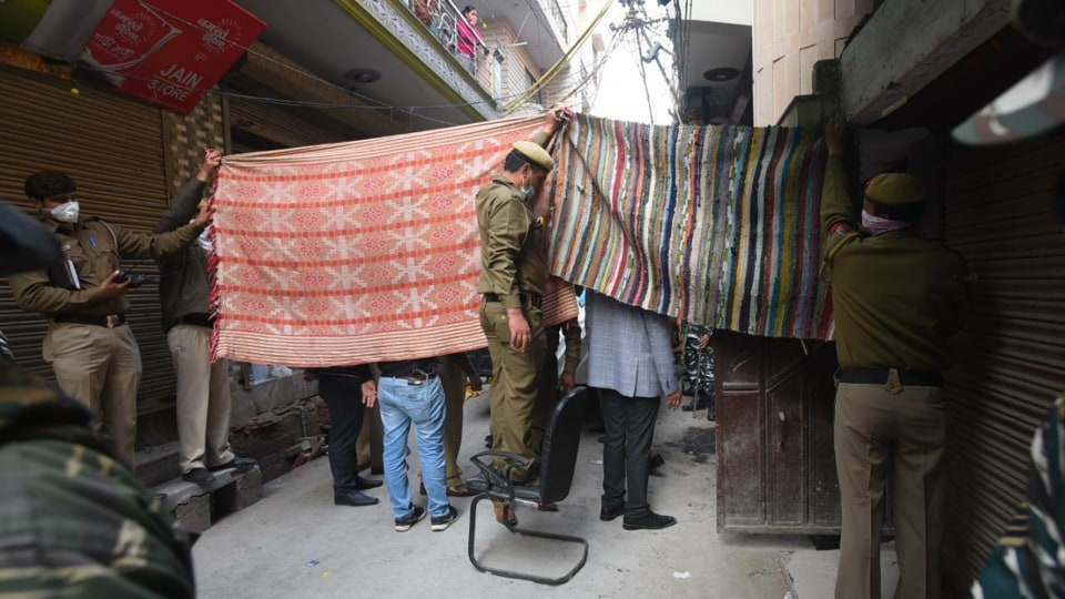 Delhi police officials covering the entrance of the house where the family of five lived in east Delhi's Bhajanpura.