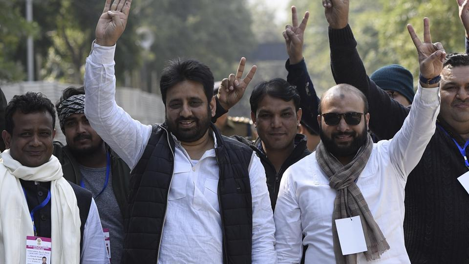 AAP candidate Amanatullah Khan from Okhla constituency shows the victory sign along with his supporters. (Photo by Burhaan Kinu / Hindustan Times)