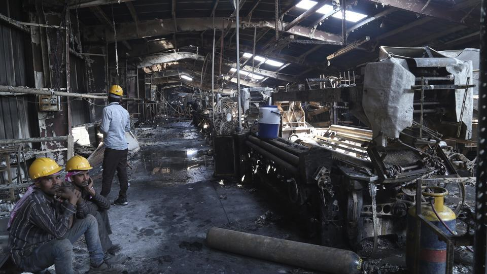 "Labourers sit near burnt remains in the factory.Surviving workers, who are paid about Rs25 per hour, said conditions had been dangerous. ""We work almost 14 hours a day. But do we have an option?"" said Vimalbhai, a textile worker, who goes by only one name. ""Every once a while there is a fire in some factory or the other. Nobody cares and we keep on working."" (AP Photo)"