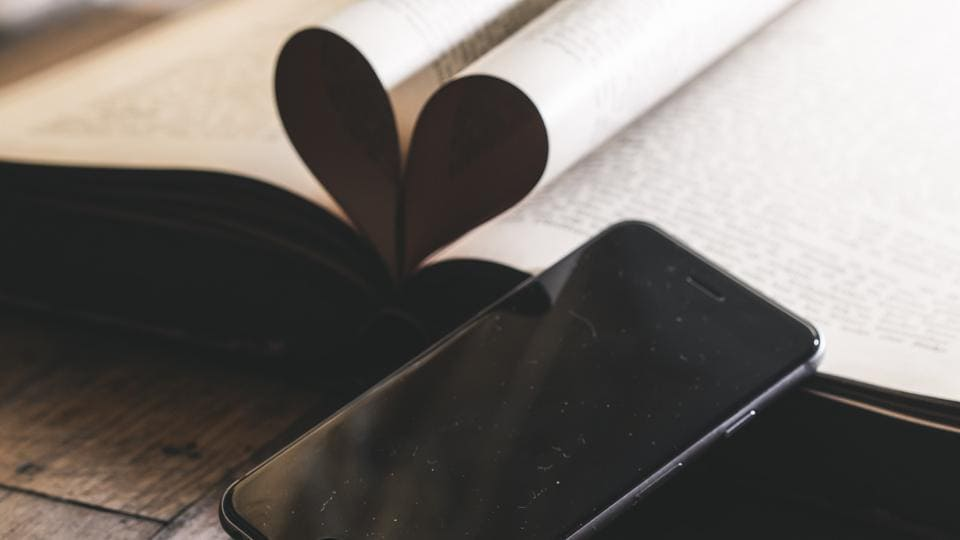 Phone with a heart made by folding two pages.