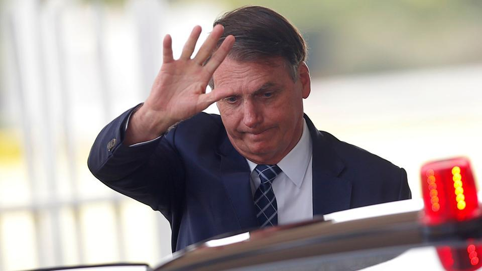 Brazil's President Jair Bolsonaro gestures as he leaves the Alvorada Palace in Brasilia, Brazil.