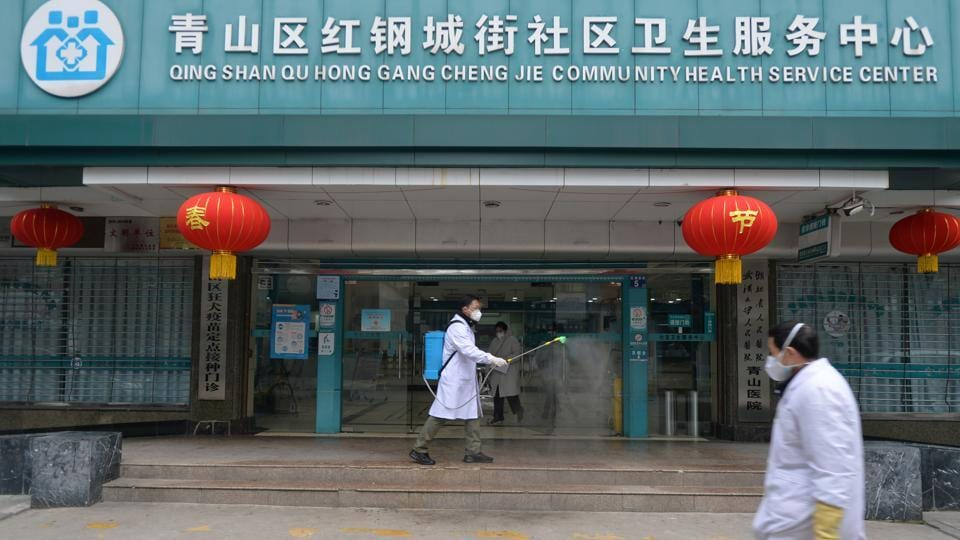 A doctor disinfects the entrance of a community health service center, which has an isolated section to receive patients with mild symptoms caused by the novel coronavirus and suspected patients of the virus, in Qingshan district of Wuhan, Hubei province.