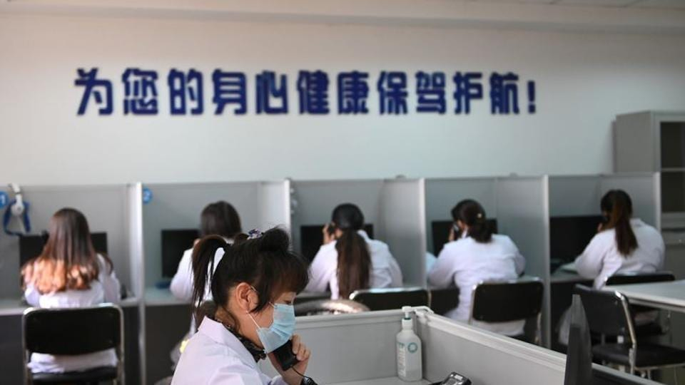 A hotline operator for free counselling service answers a phone onFebruary 12 while wearing a face mask, in Shenyang as China is hit by an outbreak of the novel coronavirus.