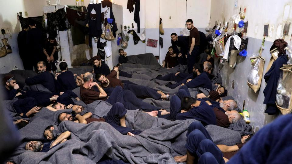 Foreign prisoners, suspected of being part of the Islamic State, in a prison cell in Hasaka, Syria. In the country's northeast, prisons and detention camps hold thousands of men, women and children whose lives are in limbo nearly a year after the final defeat of Islamic State to which they once belonged. (Goran Tomasevic / REUTERS)