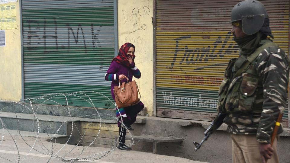 A woman crosses barbed concertina wire as a soldier stands guard during restrictions in downtown area of Srinagar, Jammu and Kashmir.
