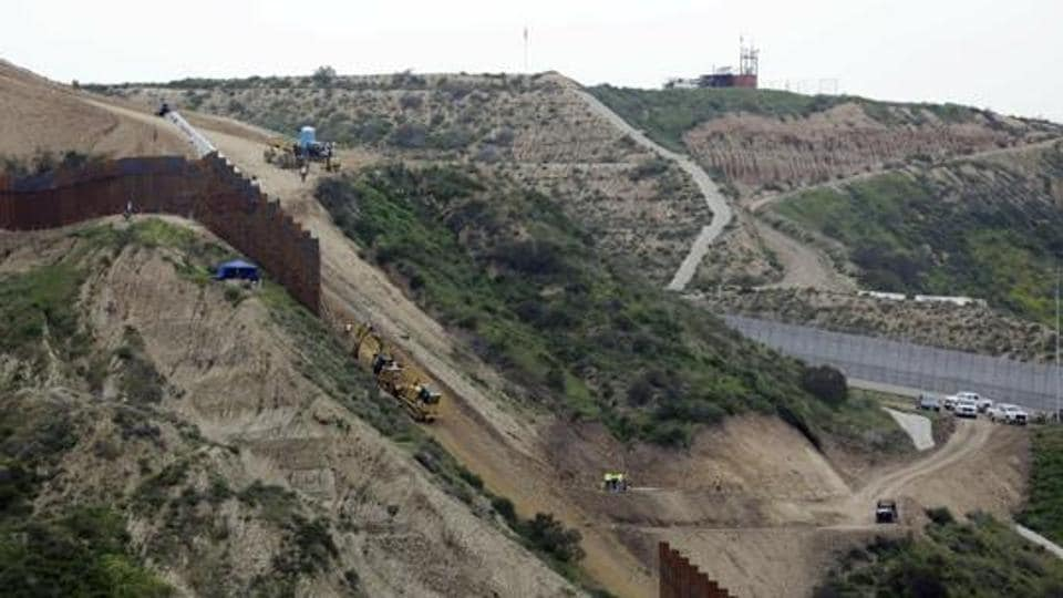 Construction crews replace a section of the primary wall separating San Diego, above right, and Tijuana, Mexico, below left, seen from Tijuana, Mexico in March 2019.