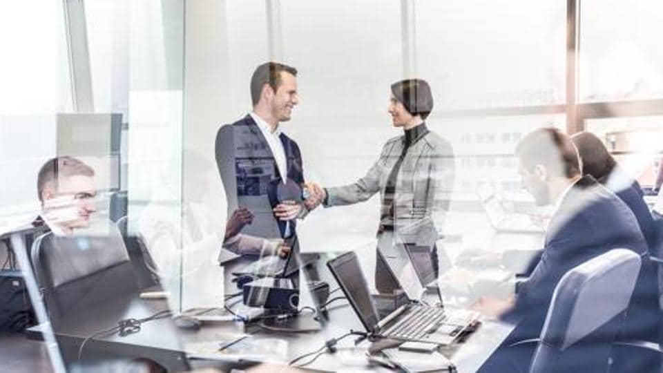 Sealing a deal. Business people shaking hands, finishing up meeting in corporate office. Businessmen working on laptop seen in glass reflection. Business and entrepreneurship concept.