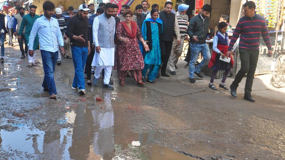 Chandigarh mayor Raj Bala Malik (centre) walking through a potholed road at Kishangarh village in Chandigarh on Thursday.
