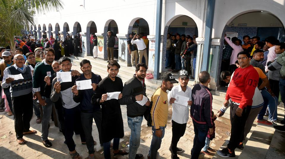People queue up to cast their votes during Delhi assembly election  on February 8.
