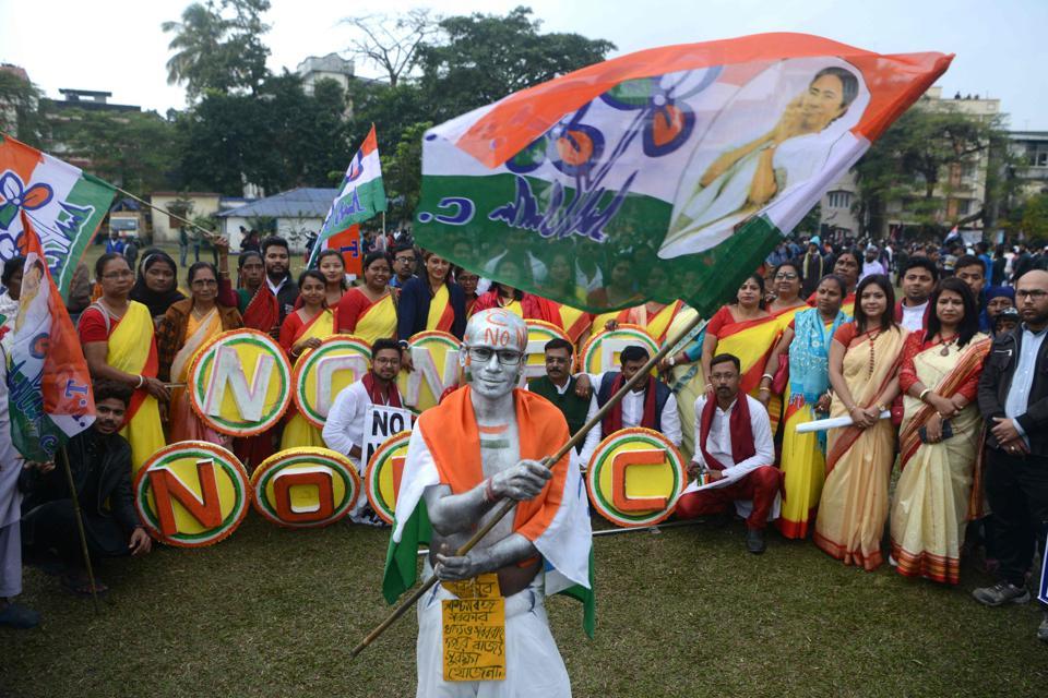 A demonstrator dressed as Mahatma Gandhi waves a flag in Siliguri.