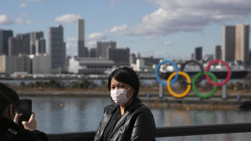 A tourist wearing a mask poses for a photo with the Olympic rings in the background, at Tokyo's Odaiba district.
