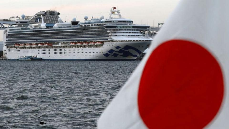 The cruise ship Diamond Princess is pictured beside a Japanese flag as it lies at anchor while workers and officers prepare to transfer passengers who tested positive for coronavirus.