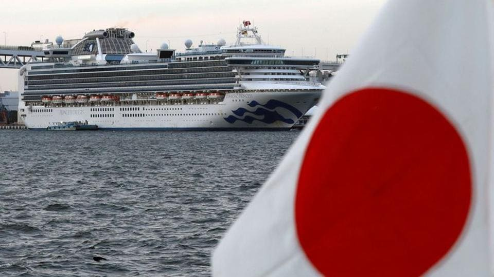 The cruise ship Diamond Princess is pictured beside a Japanese flag as it lies at anchor while workers and officers prepare to transfer passengers who tested positive for coronavirus, at Daikoku Pier Cruise Terminal in Yokohama, Japan.