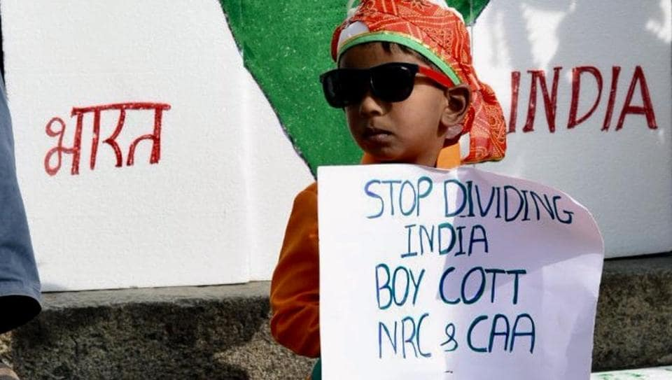 A child holds a placard during a protest against CAA in front of Town Hall in Bengaluru.