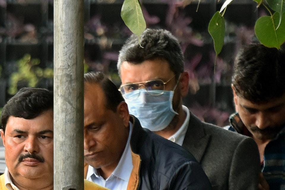 Sanjeev Chawla (wearing a mask) is being taken into police custody after he was brought to New Delhi from London on Thursday.
