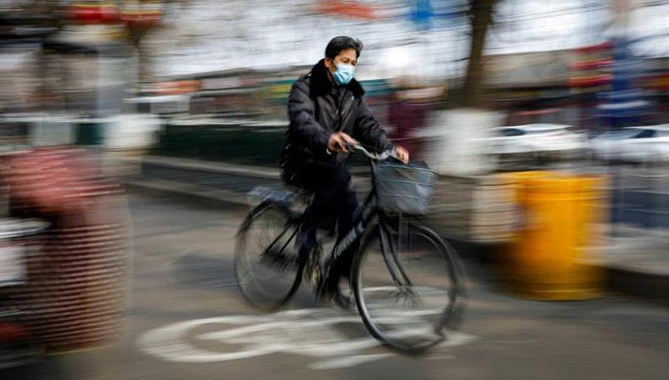 A man wearing a face mask rides a bicycle, as the country is hit by an outbreak of the novel coronavirus, in Beijing, China .