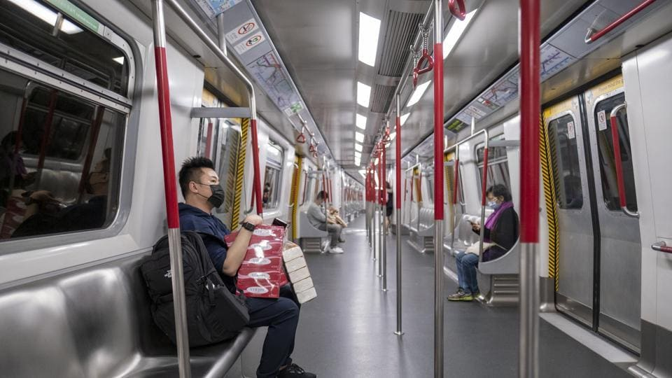 A passenger wearing a protective face mask carries packs of tissues while riding a subway train in Hong Kong, China, on Friday, Feb. 14, 2020.
