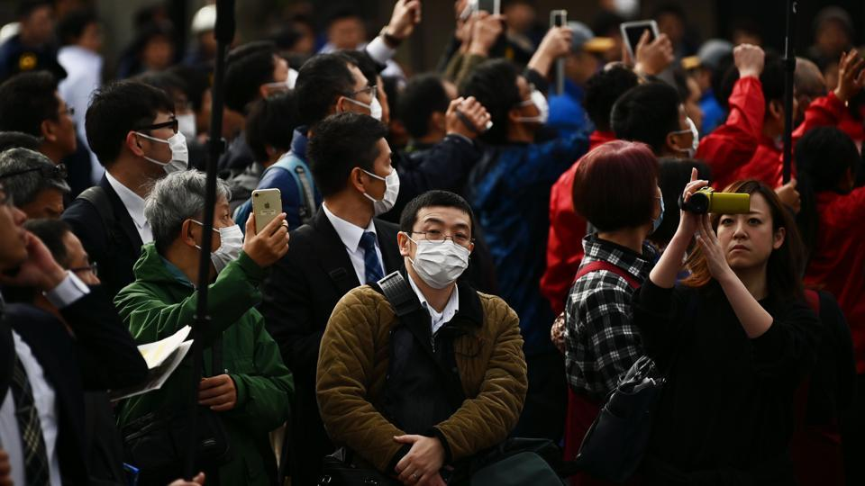 People  wearing facemasks look on during a rehearsal of the Tokyo 2020 Olympics torch relay in Tokyo on February 15, 2020.
