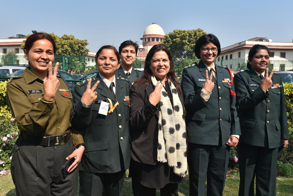 Lt. Col. Seema Singh (2R) and other women army personnel show victory signs with their lawyer Meenakshi Lekhi (C) after the apex court's decision to apply permanent commission to all women officers in the Indian Army, at Supreme Court, in New Delhi on Monday.