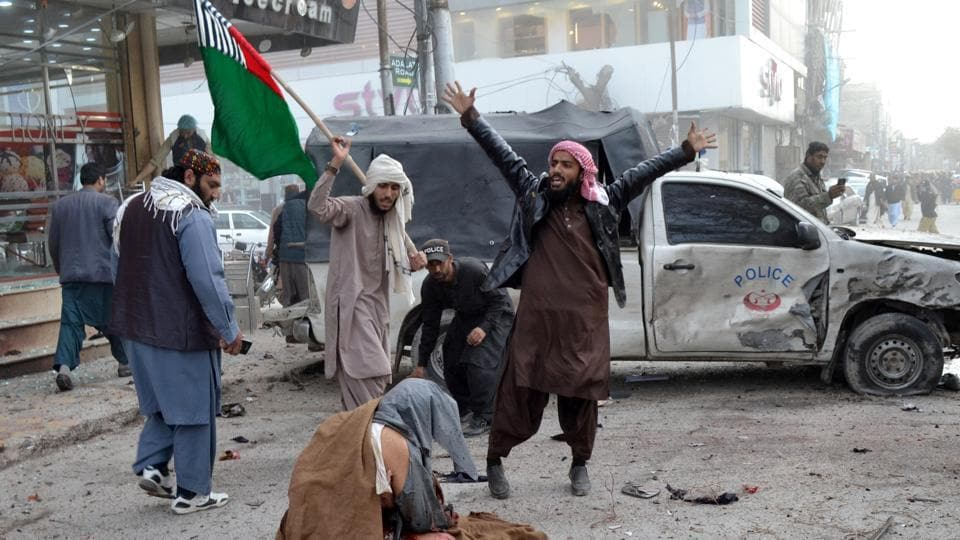 People react as a wounded man sits on the ground after a bomb blast in Quetta, Pakistan.