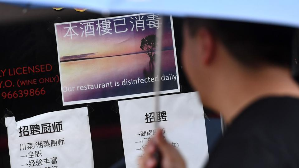 A passer-by looks at a sign from a Chinese restaurant stating it is disinfected daily, in Melbourne's Chinatown. Streets are notably quieter, face masks are commonplace and even a Lunar New Year dragon dance failed to bring in the crowds. Businesses report their earnings have dropped by more than half and they have been forced to cut staff hours dramatically, a situation echoed in Chinatowns across the world. (William West / AFP)