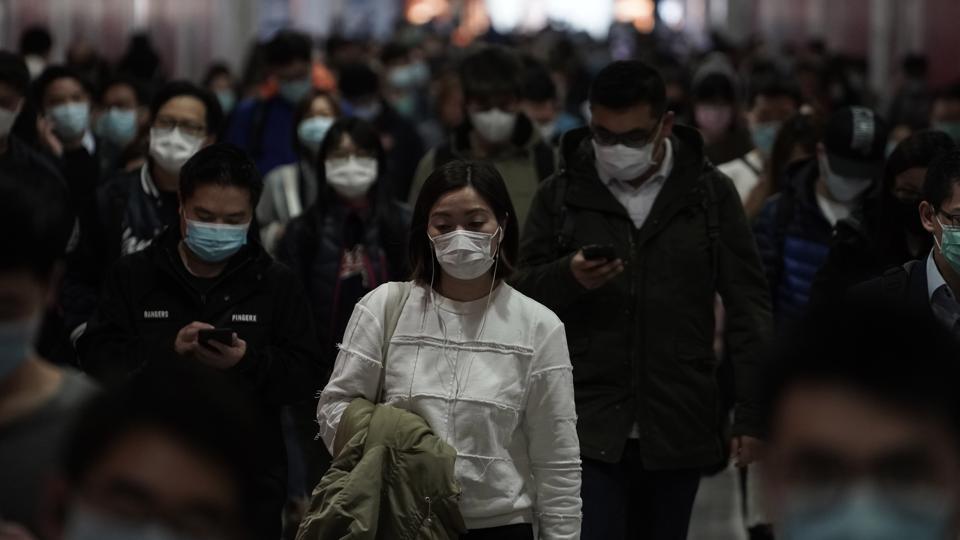 People wearing masks, walk in a subway station, in Hong Kong, Friday, Feb. 7, 2020.