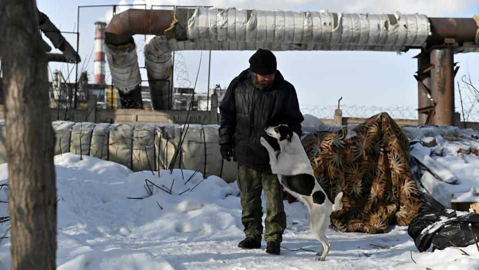 """Alexei Vergunov, nicknamed """"Lyokha Boroda"""" (Lyokha the beard), who is homeless, stands near his makeshift shelter with his dog Bella, in Omsk, Russia. Like many of Siberia's homeless, Alexei Vergunov survives freezing night-time temperatures of -30 degrees Celsius by sleeping under an industrial heating pipe for warmth. (Alexey Malgavko / REUTERS)"""