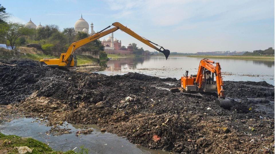 Earthmovers remove debris from the Yamuna river bed near Taj Mahal, ahead of the US President Donald Trump's visit, in Agra, Uttar Pradesh. (PTI)