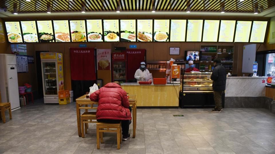 It is lunch time in Beijing, but the only diner in Cindy's Cafe is an employee having a staff meal—it has been closed for more than three weeks as China battles a deadly virus epidemic. At Cindy's Cafe in Beijing's Roosevelt Plaza, dine-in revenue has fallen to zero, and relying on deliveries hardly makes up the shortfall, manager Cai Yaoyang told AFP. (Greg Baker / AFP)