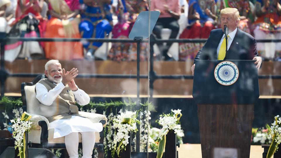 "US President Donald Trump speaks as Prime Minister Narendra Modi smiles during 'Namaste Trump' event. ""I have travelled 8,000 miles across the globe to convey just a message that America loves India. US respects India, will be a faithful and loyal friend, ""said Trump. (Money SHARMA / AFP)"