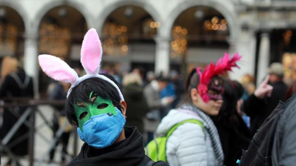 A carnival reveller wears a protective mask at Venice Carnival, which the last two days of, as well as Sunday night's festivities, have been cancelled because of an outbreak of coronavirus, in Venice, Italy February 23, 2020.