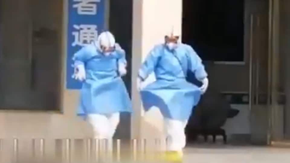 Two medical professionals are seen dancing.