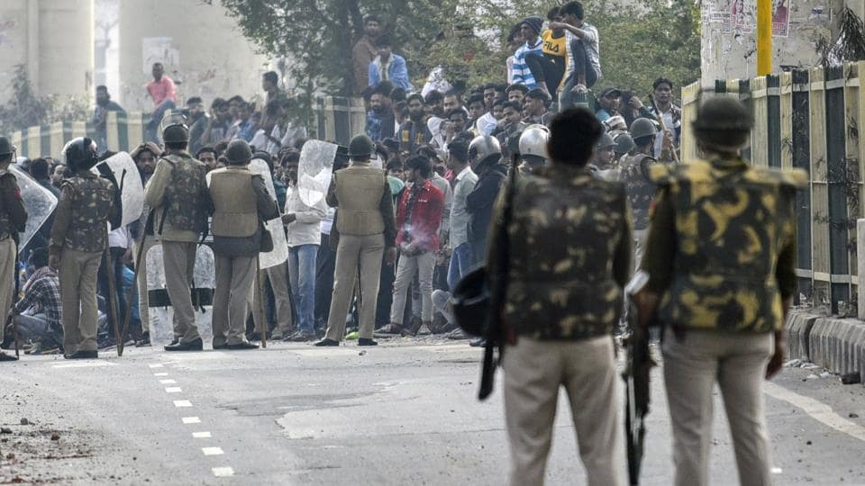 Police personnel try to stop demonstrators at Jafrabad-Maujpur road in New Delhi after clashes and stone-pelting between pro- and anti-CAA groups, on Tuesday.