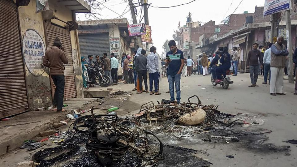Passersby look at the charred remains of vehicles which were set ablaze by rioters during clashes over the new citizenship law, at Mustafabad area of East Delhi.
