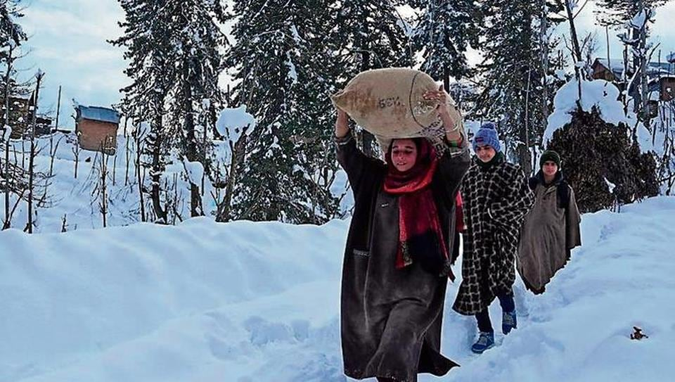 Villagers carry rice after heavy snowfall in Budgam district of Srinagar on January 18.
