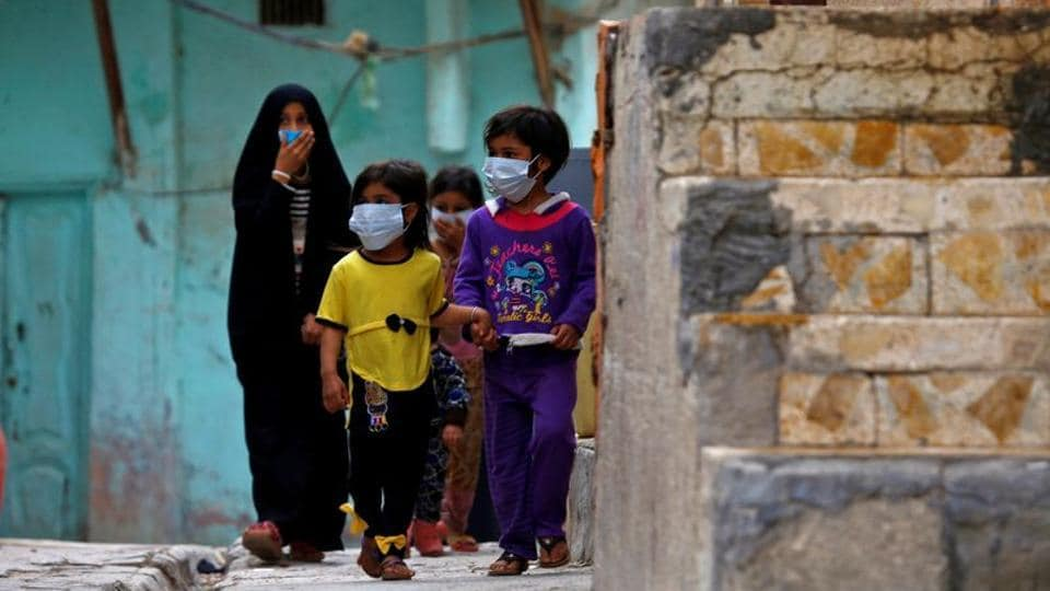 Iraqi children wear protective masks as they walk near a religious school where the first coronavirus case was detected, following the outbreak of the new coronavirus, in the holy city of Najaf, Iraq.