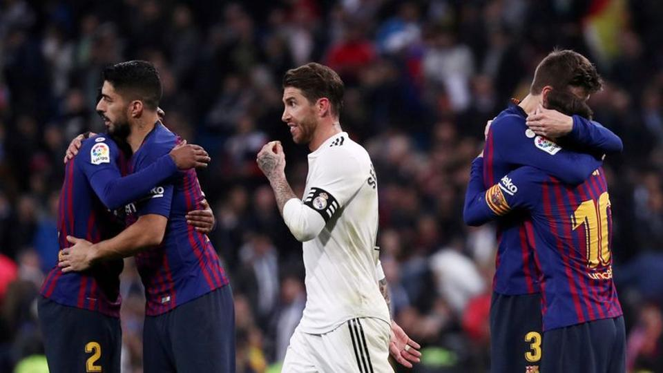 FILE PHOTO: Soccer Football - La Liga Santander - Real Madrid v FC Barcelona - Santiago Bernabeu, Madrid, Spain - March 2, 2019 FC Barcelona's Lionel Messi, Luis Suarez and Gerard Pique celebrate victory as Real Madrid's Sergio Ramos walks off REUTERS/Sergio Perez