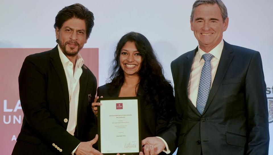 Indian bollywood actor Shah Rukh Khan (L) and Australia Chancellor of La Trobe University, Australian John Brumby (R) pose for pictures during the La Trobe University PhD scholarship to PhD research student Gopika Kottantharayil Bhasi (C)at the Indian Cinema Attraction Fund and 10th Indian Film Festival of Melbourne Celebration, in Mumbai on February 26, 2020.