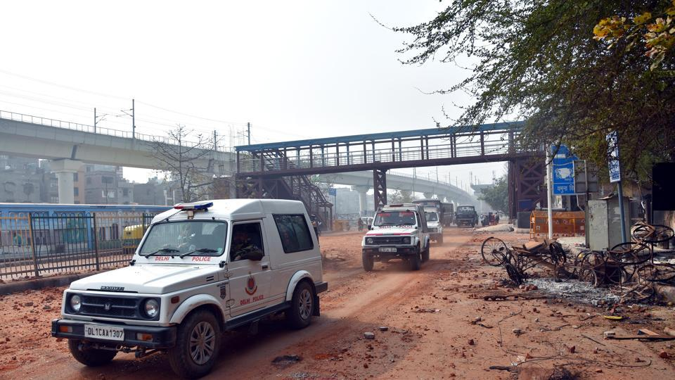 Police vehicles patrol the roads in violence-hit northeast Delhi on Wednesday.