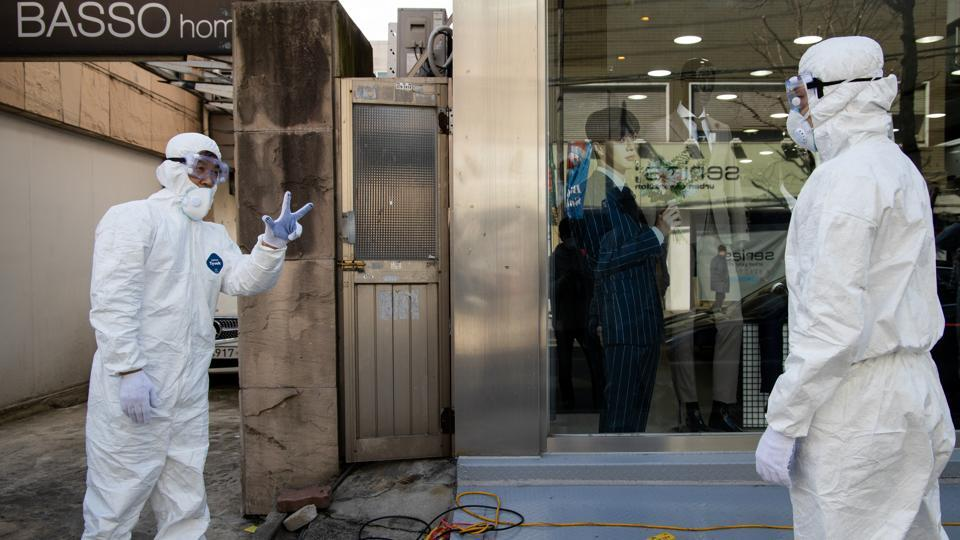 Workers wearing protective suits talk outside a clothing store on Munjeong-dong Rodeo Street in the Songpa district of Seoul, South Korea.